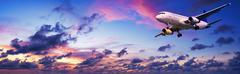 jet aircraft is maneuvering for landing in a spectacular sunset sky. panorami - stock photo