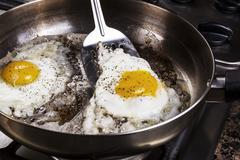 Eggs cooked with bacon grease in pan Stock Photos