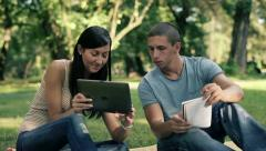 Young students with tablet computer in the park, steadicam shot HD - stock footage