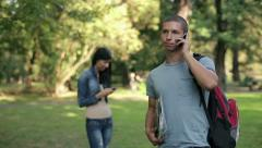 Young student talking on cellphone in the park, steadicam shot HD - stock footage