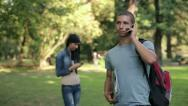 Stock Video Footage of Young student talking on cellphone in the park, steadicam shot HD