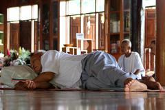 Man sleeping in buddhist temple Stock Photos