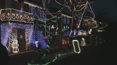 Stock Video Footage of Festive flashing lights adorn house in winter.
