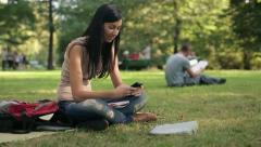 Young teenage student with smartphone in the park HD Stock Footage