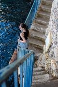 Brunette woman standing at a blue railing Stock Photos