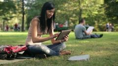 Young female student with tablet computer in the park HD Stock Footage