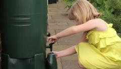 9 year old caucasian girl in summer dress fills green watering Stock Footage