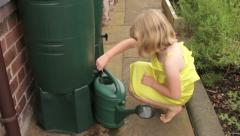 9 year old caucasian girl in summer dress fills green watering can Stock Footage