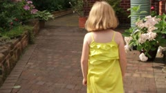 9 year old caucasian girl in summer dress walking round house is followed Stock Footage