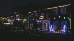 Stock Video Footage of Festive flashing lights adorn 2 houses in winter