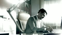 Stock footage man signs documents in his office Stock Footage