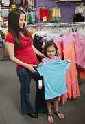 Sekarotuinen äiti ja tytär ostokset lasten vaatteet Kuvituskuvat