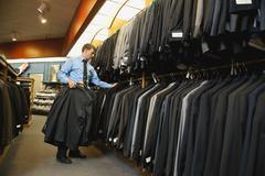 Caucasian man working in men's clothing store Stock Photos