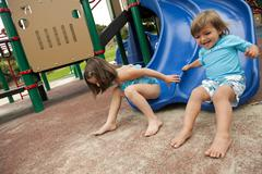 Brother and sister sliding down slide on playground Stock Photos