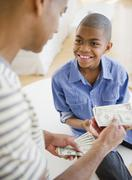 Father giving son money Stock Photos
