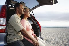 Black couple sitting on hatchback enjoying the beach - stock photo