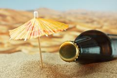 bottle under an umbrella on the sand - stock photo
