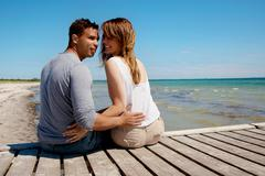 attractive couple sitting on a pier - stock photo