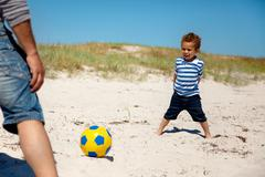 little kid playing football with dad - stock photo