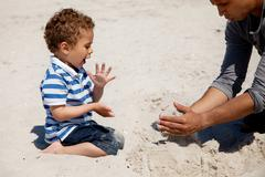 kid looking as his dad makes sand castle - stock photo
