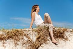 woman sitting on sand dunes - stock photo