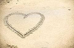 heart shape drawn on sand - stock photo