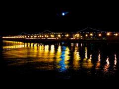 The San Francisco Oakland Bay Bridge reflecting into the bay at nightime Stock Photos