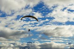 Tandem Paragliders Against Cloudy Sky In Ecuadorian Andes In The Background Stock Photos