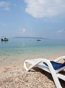 Deck chair on beach with a view at blue sea and island hvar - stock photo