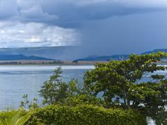 rain falling on inland hydroelectric lake furnas - stock photo