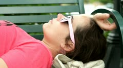 Female laying on park bench with sunglasses Stock Footage