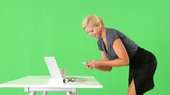 Provocative businesswoman standing by desk and using cellphone Stock Footage