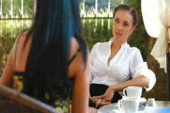 Female Friends Talking at Urban Cafe Stock Footage