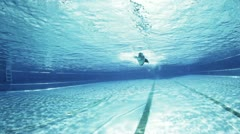Freestyle swimmer under water passing camera Stock Footage