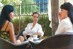 Three Women Talking at Outdoor Cafe Stock Footage