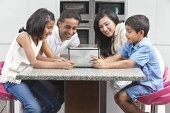Asian indian family using tablet computer at home Stock Photos
