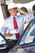 Businessman architect in hard hat on cell phone by car Stock Photos