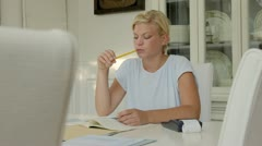 Young woman checking bills and doing budget at home - stock footage