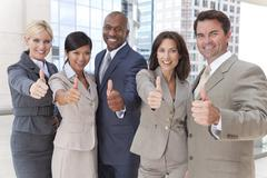 Interracial men & women business team thumbs up Stock Photos