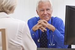 Stock Photo of senior male doctor with female patient