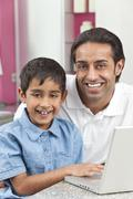 Asian indian father & son using laptop computer at home Stock Photos