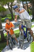 African american man & boy, father and son riding bikes Stock Photos