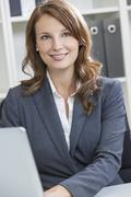 Beautiful woman or businesswoman in office Stock Photos