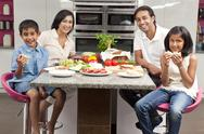 Asian indian parents children family eating healthy food in kitchen Stock Photos