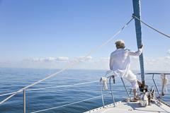 senior woman on the bow of a sail boat - stock photo