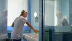 Young woman doing chores and cleaning bathroom at home - stock footage