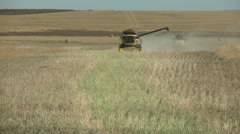 Agriculture, Fall harvest, yellow combine head on, wheat field Stock Footage