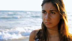 sad girl thinking on a beach during sunset closeup - stock footage