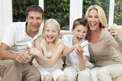 happy family having fun playing video console games - stock photo