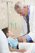 young boy child patient in hospital bed & male doctor - stock photo
